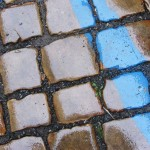 Rain, cobblestones, and blue stripe in the streets of Prague.