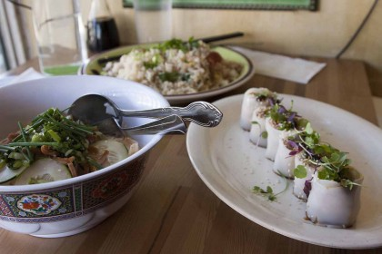 On the left, a bowl of Fresh Rice Noodles with Peanut Sauce, Tofu, and Pickled Mustard Greens, in the back is the Salt Cod Fried Rice and on the right, a row of Tea Smoked Eel.