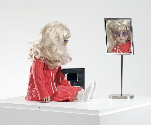 Lynn Hershman Leeson, CyberRoberta, 1996. Custom-made doll, clothing, glasses, webcam, surveillance camera, mirror, original programming, and telerobotic head-rotating system, Aprox. 17 ¾ x 17 ¾ x 7 ⅞ in